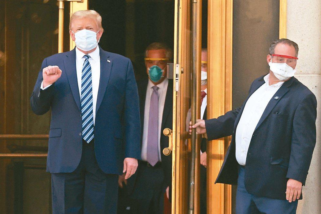 美國總統川普(左)5日在步出華特里德軍醫院準備返回白宮前,握拳向媒體致意。路透
