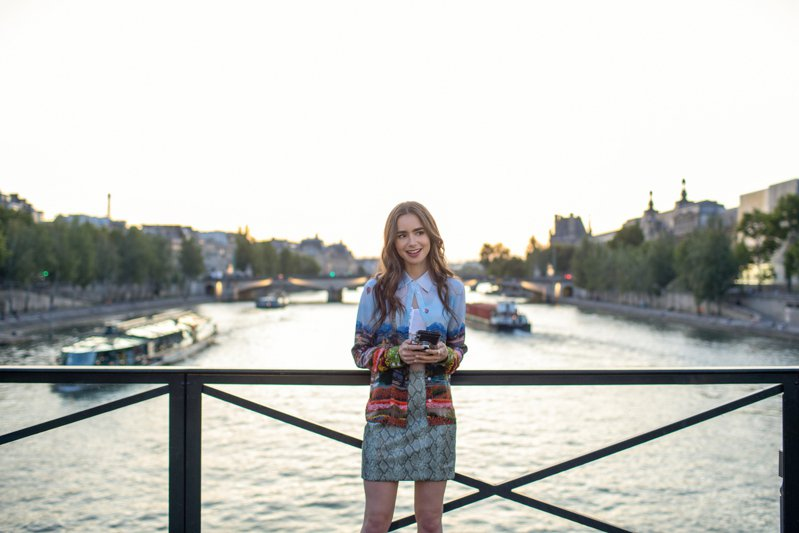 艾蜜莉到公司報到時,選穿Alice+Olivia 的艾菲爾印花襯衫、Ronny Kobo蟒蛇紋迷你裙。圖/NETFLIX提供