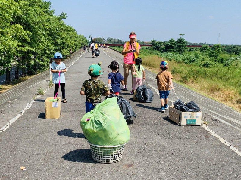 國慶連假第一天,台南一群媽媽帶著學齡前孩子,一起到麻豆堤防撿拾垃圾。圖/主辦單位提供