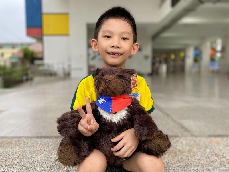 嘉義市精忠國小學生,帶台灣黑熊造型泰迪熊、繫上國旗領巾在校園拍照,寄給日本友人。圖/精忠國小提供