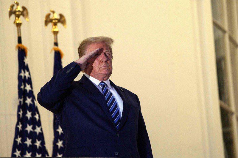美國總統川普5日從軍醫院返回白宮後,脫下口罩向總統專用直升機「陸戰隊一號」敬禮。法新社