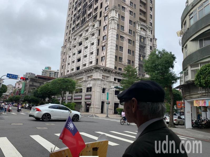 今天是國慶日,今年73歲的張姓舉牌工人,上工裝備除了建案宣傳牌,他也從家裏翻出小國旗,夾在建案牌上。記者趙宥寧/攝影