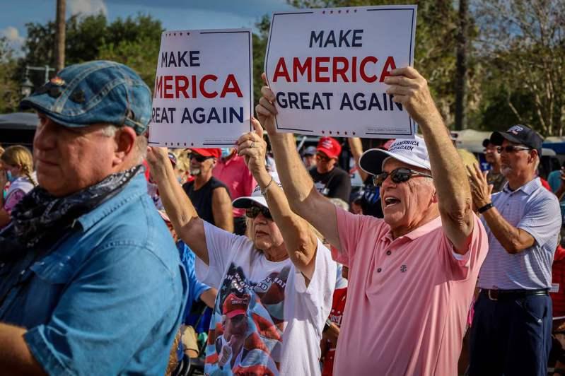 美國總統川普至今仍有許多死忠支持者,不戴口罩參與競選造勢活動。圖為佛州10日的一場造勢會,副總統潘斯發言時,選民高舉標語「讓美國再次偉大」。法新社
