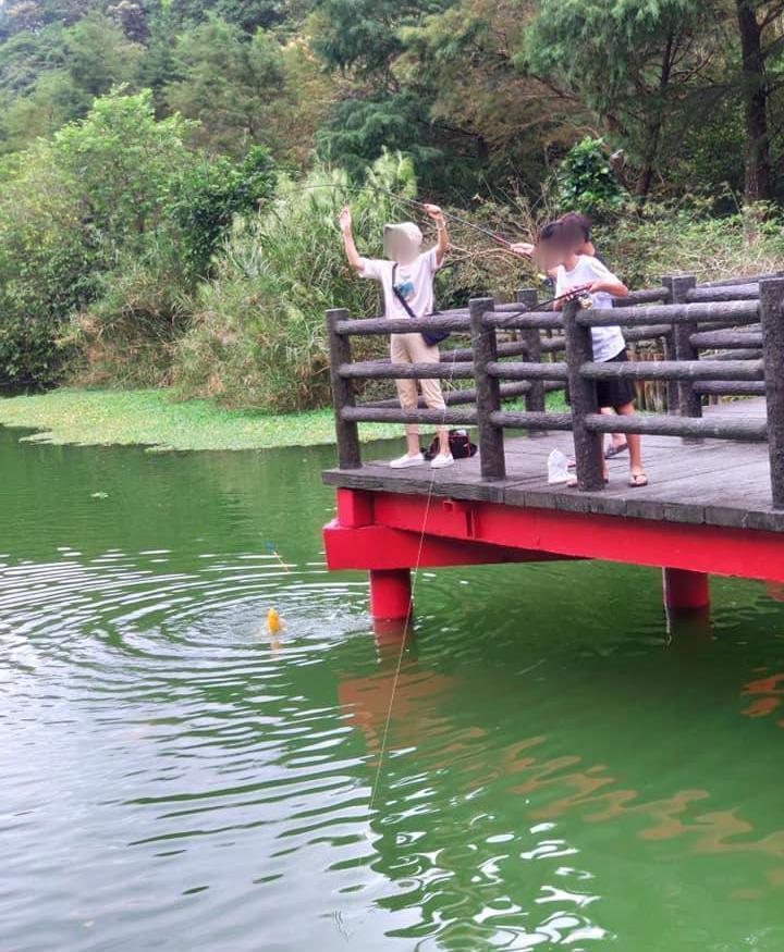 宜蘭望龍埤出現疑似媽媽帶著兩個小孩在湖邊釣鯉魚的離譜事件。 圖擷自爆料公社