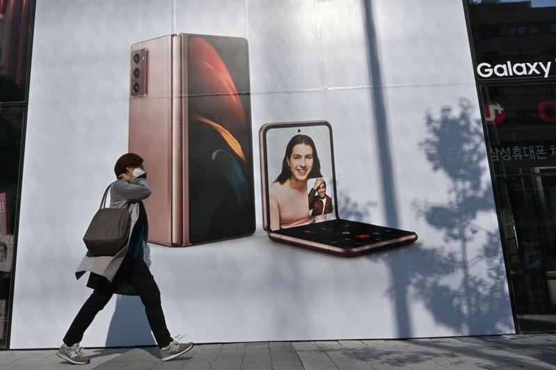 網友詢問Android哪裡比iOS好。圖為一名女子走過三星Galaxy Z Fold2和Galaxy Z Flip廣告海報。法新社