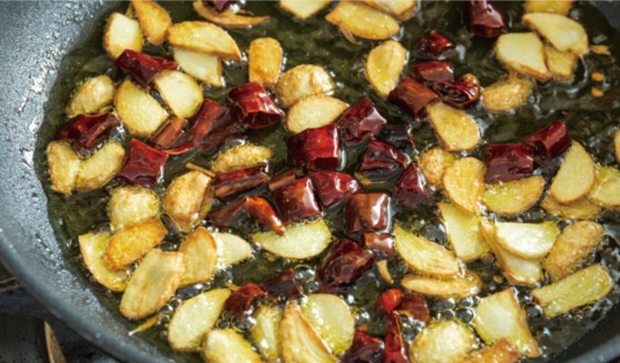 將蒜片與乾辣椒放入熱油中,煸到香氣出來且變色即可,注意蒜片不要煸過久,以免產生苦...
