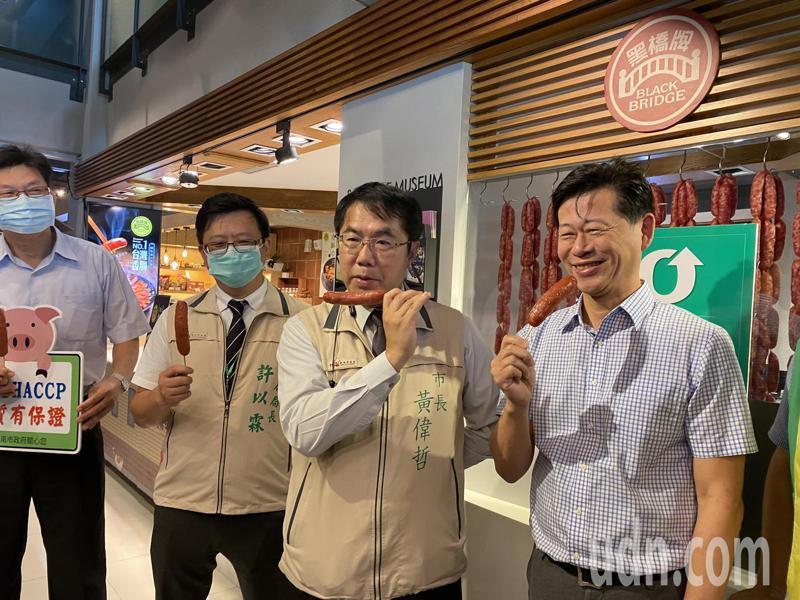 台南市長黃偉哲(右二)今天到黑橋牌香腸的工廠內,與黑橋牌董事長陳春利(右)一起大啖香腸。記者修瑞瑩/攝影