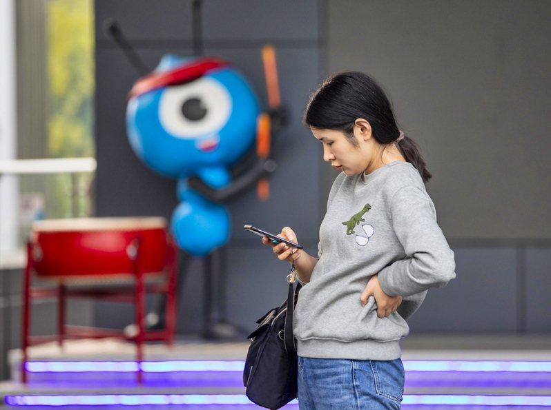 螞蟻集團的支付網絡去年有10億使用者,完成16兆美元的交易,連上8000萬家商店。圖為一名使用者在杭州螞蟻集團總部前使用手機。歐新社