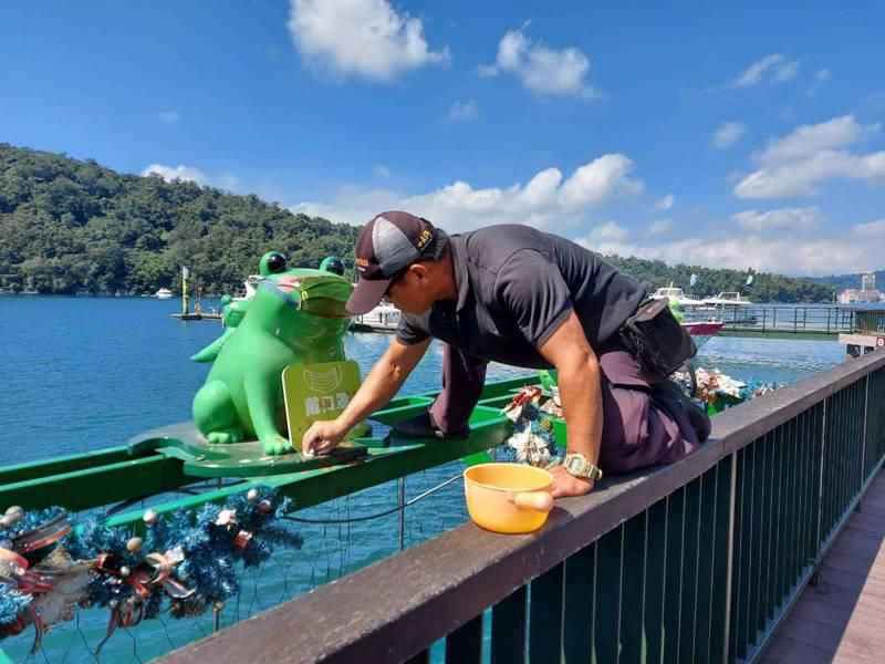 日月潭伊達邵碼頭上的水蛙裝置藝術,工作站人員上午發現被人吐滿了檳榔汁,已加派人手清潔中。圖/日管處提供