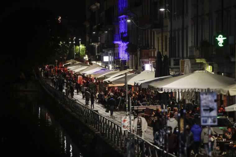 義大利實施嚴格防疫規定,餐廳酒吧晚間有限度開放。圖為米蘭知名夜生活運河區13日依...