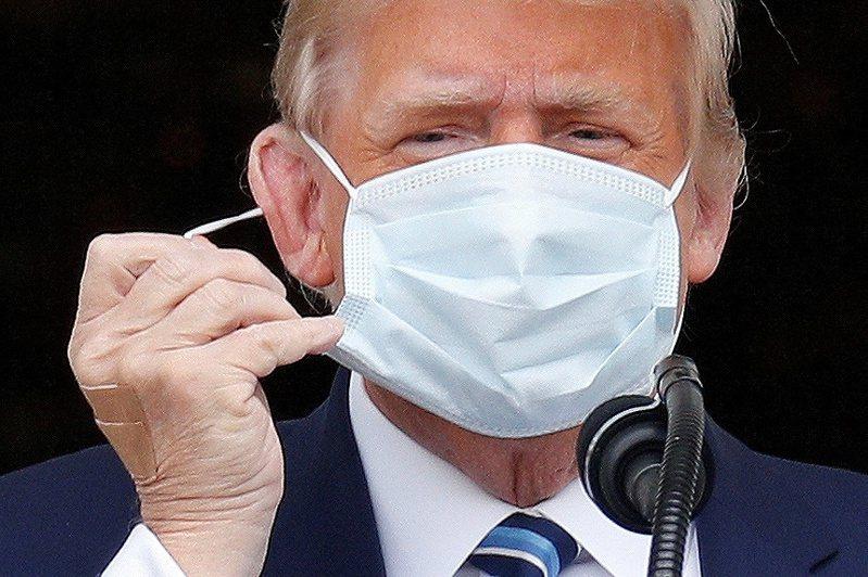 美國總統川普10日在白宮準備對群眾發表演說,第一個動作就是脫掉口罩。 路透