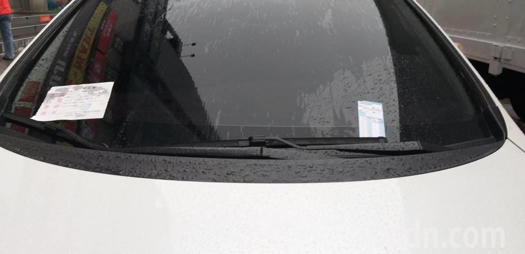 一名女子把五門轎車停在「貨車裝卸專用區」,右雨刷夾了停車收費單,左雨刷夾了逕行舉...