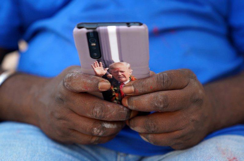 基許納的手機背面貼了川普的肖像。 路透