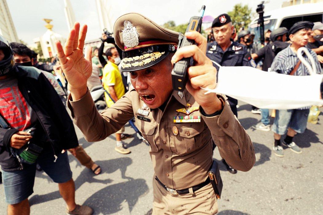 尿急面前,人人平等。圖為14日集會現場一名貌似驚慌的泰國警察。 圖/路透社