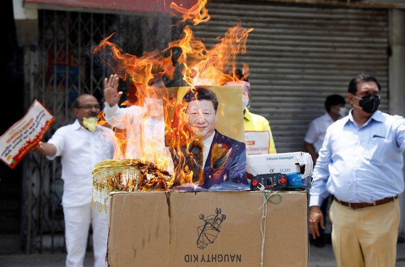 今年5月中印邊境對峙以來,地區緊張局勢持續升溫。圖為新德里6月22日有民眾抗議中國,且在活動中焚燒中國大陸國家主席習近平的照片。路透