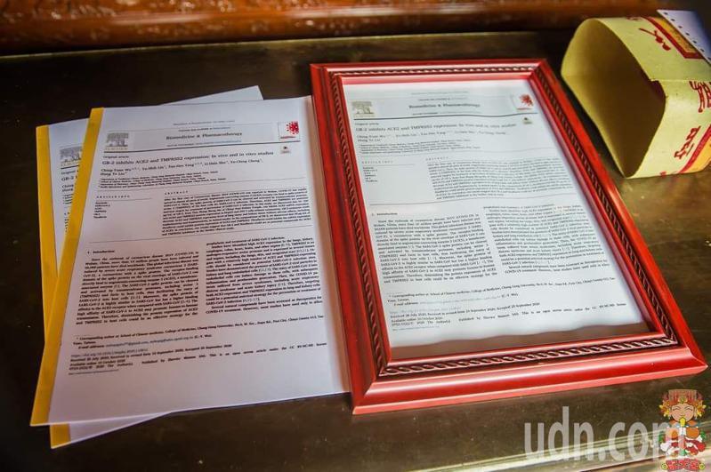 嘉義長庚醫院中醫科主任吳清源將裝框影印研究預防新冠病毒感染論文獻給朴子市配天宮媽祖答謝。圖/配天宮提供