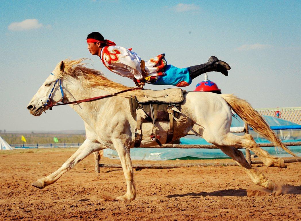 内蒙古鄂尔多斯成吉思汗陵附近的那达慕会场,蒙古族传统马术表演。 图/新华社