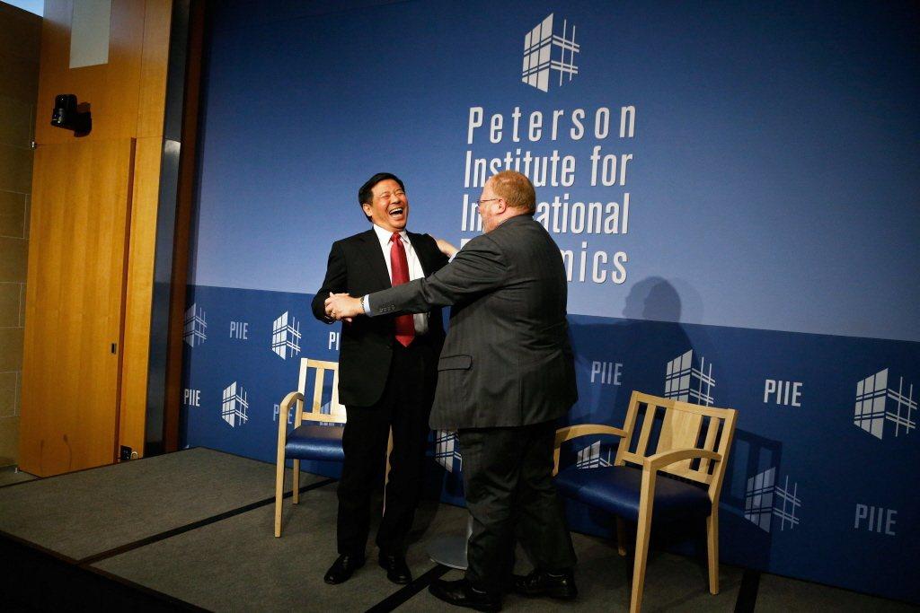 2014年,時任中國財政部副部長朱光耀與彼得森國際經濟研究所所長,參與該所舉辦的全球經濟問答。 圖/路透社