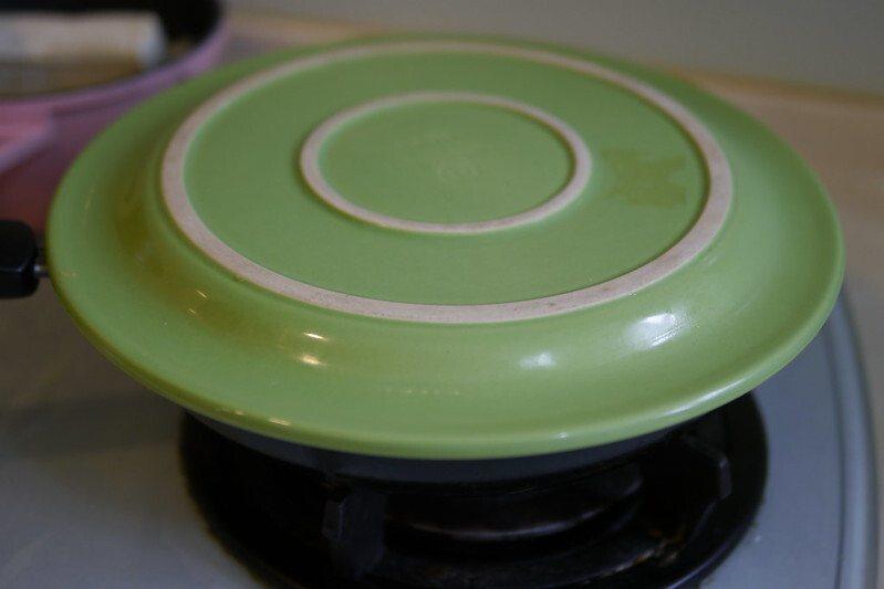 用一個比平底煎鍋或深鍋大一點的盤子,扣在鍋子上,圓形蛋餅平整的翻轉倒扣在盤子上,再將蛋餅放進平地鍋內繼續間煎另一面