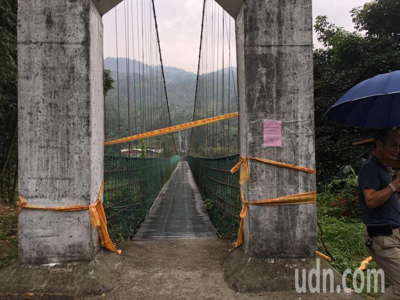 嘉義縣梅山鄉太興村「瑞興觀光吊橋」繩索斷裂,鄉公所拉封鎖線,在橋頭張貼禁止行走公告。圖/讀者提供