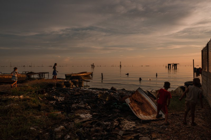委內瑞拉卡維馬斯市的孩童在廢漁船碼頭玩耍,廢棄煉油廠外洩的原油嚴重汙染著海岸和海面。(紐約時報)