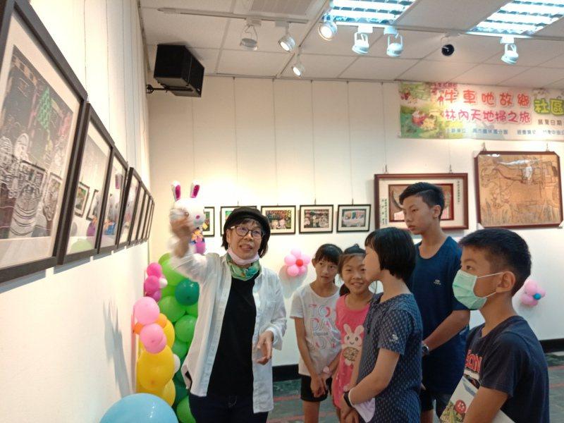 繪本美術指導老師許錦治(左一)為小朋友導覽繪本作品。圖/高市圖林園分館提供
