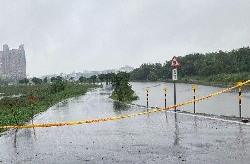 宜蘭雨勢不斷,五十二甲溼地有部分路段淹水,看不清道路,員警拉起封鎖線管制通行。圖/警方提供