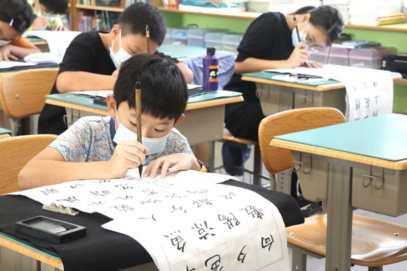 「第21屆明宗獎全國書法篆刻暨印鈕比賽」今天舉辦決賽,參賽小朋友專注寫書法。記者徐白櫻/翻攝