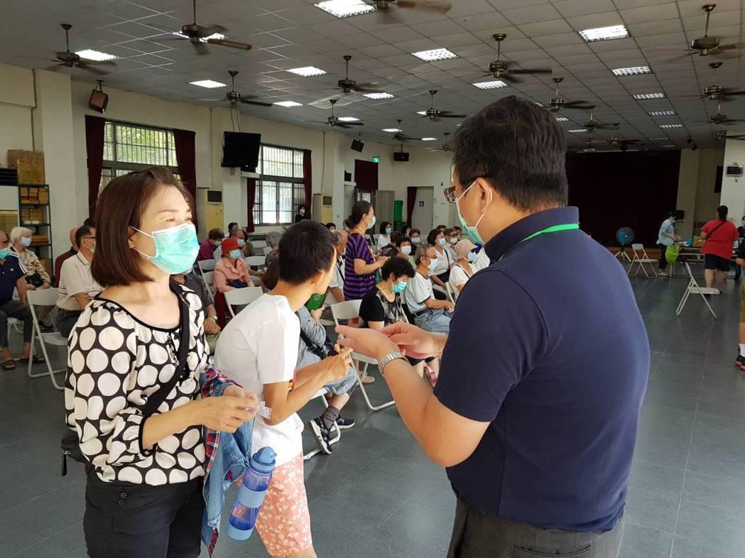 台南市衛生局局長許以霖(右)今天到北區賢北里,向民眾說明新的流感疫苗症策。圖/衛...
