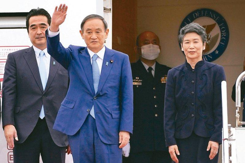 日本首相菅義偉(左二)十八日前往越南訪問,在東京羽田機場登機時向支持者揮手致意,身旁為夫人真理子(右一)。(路透)