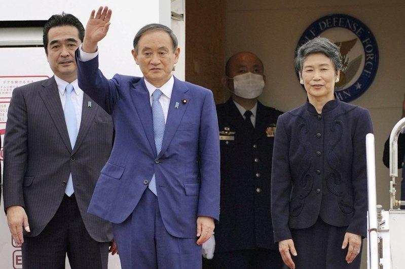 日本首相菅義偉(左二)18日前往越南訪問,在東京羽田機場登機時向支持者揮手致意,身旁為夫人真理子(右一)。(路透)