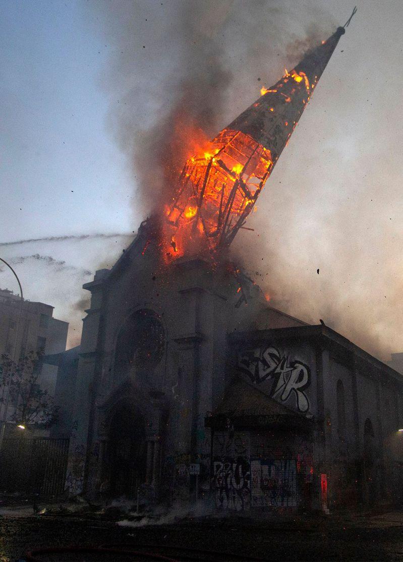 18日智利首都聖地亞哥數以萬計民眾18日上街集會,紀念去年的反政府示威一周年,警民衝突更造成一座教堂燒毀倒塌。法新