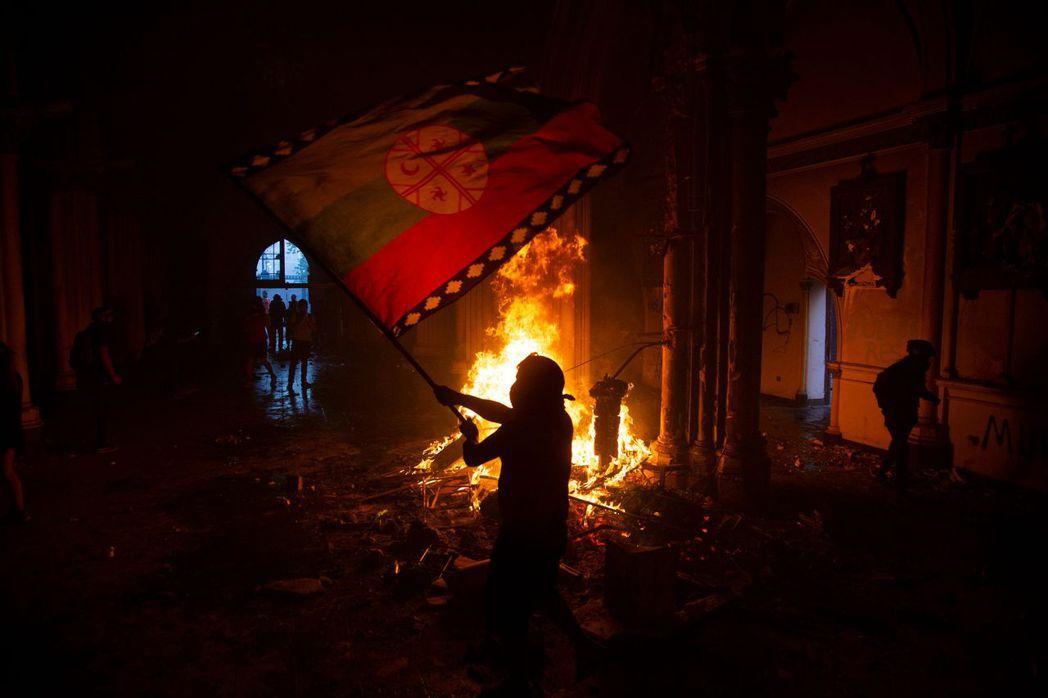《法新社》回傳的火場照片中,就能看到一名蒙面的示威者,在卡賓槍騎兵教堂內,揮舞著...