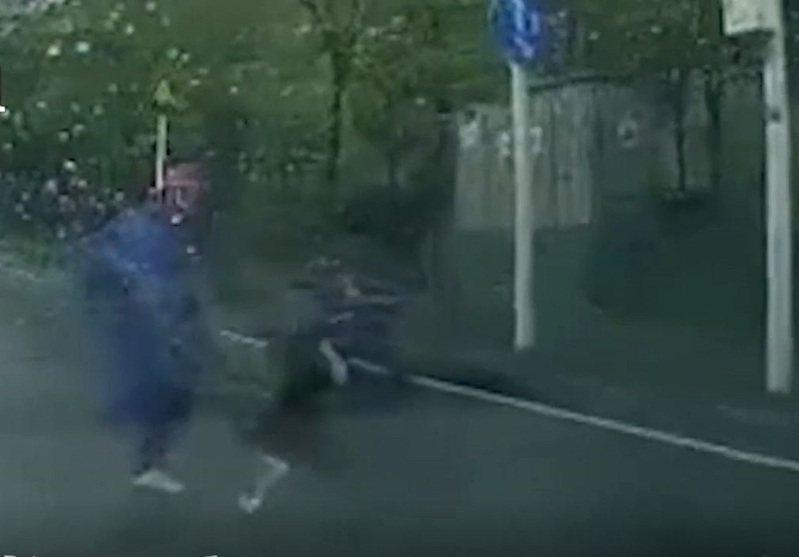 一名家長日前騎電動腳踏車載小孩出門,停等紅燈後起步時加速太快,導致小孩不慎掉落路上,這名家長完全沒察覺,仍舊繼續往前行駛,直到小孩在後方追趕上,卻被家長一腳踹倒在地。 圖/影片截圖