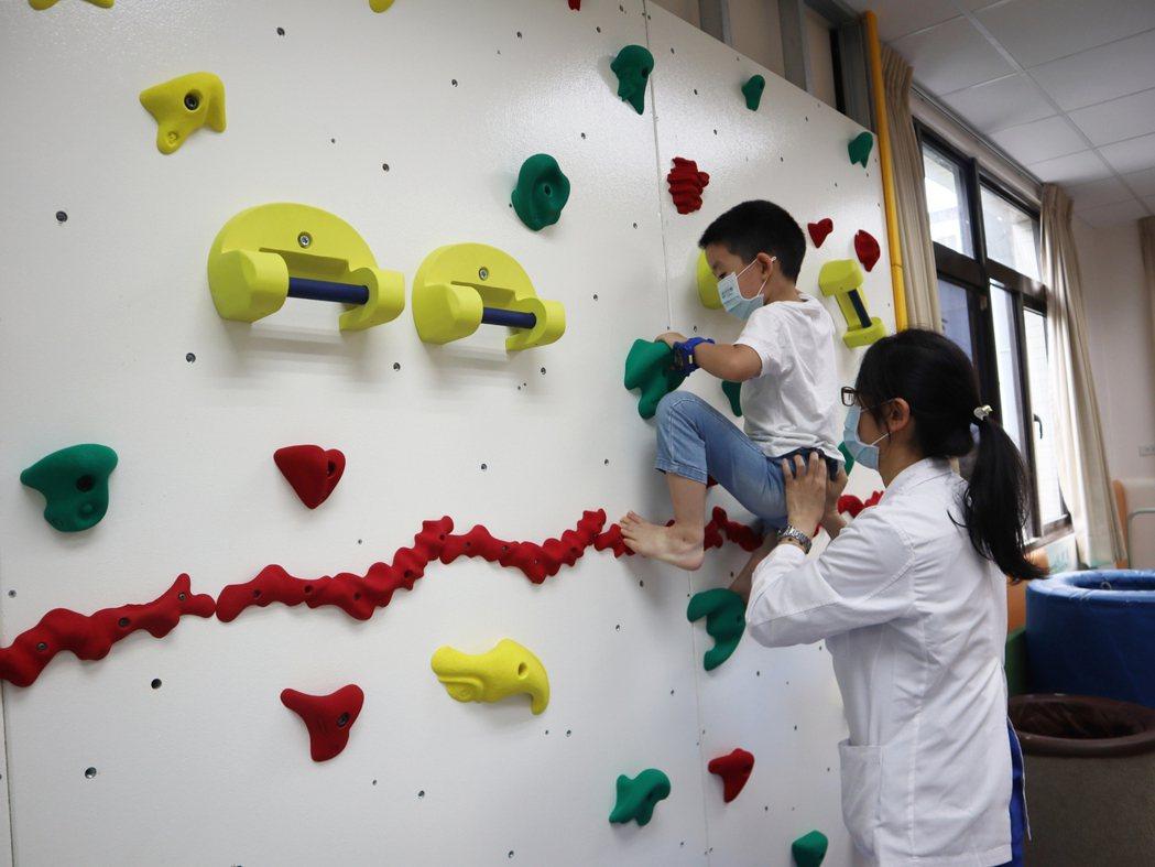 小森在治療師陪同下使用攀岩牆,訓練身體大動作的協調與計畫能力,能知道什麼時候該動...