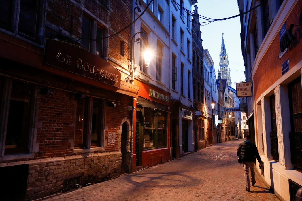 比利時全國餐館酒吧19日起關閉一個月,防止新冠肺炎傳播,一名男子當天走過布魯塞爾...