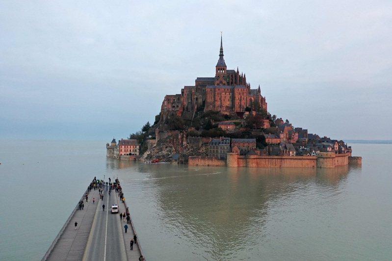法國西北的聖米歇爾山是知名觀光景點,當局數年前新修一條通行橋18日被罕見漲潮淹過,數十名遊客就站在橋面遠眺再成海中孤島的聖米歇爾山。法新