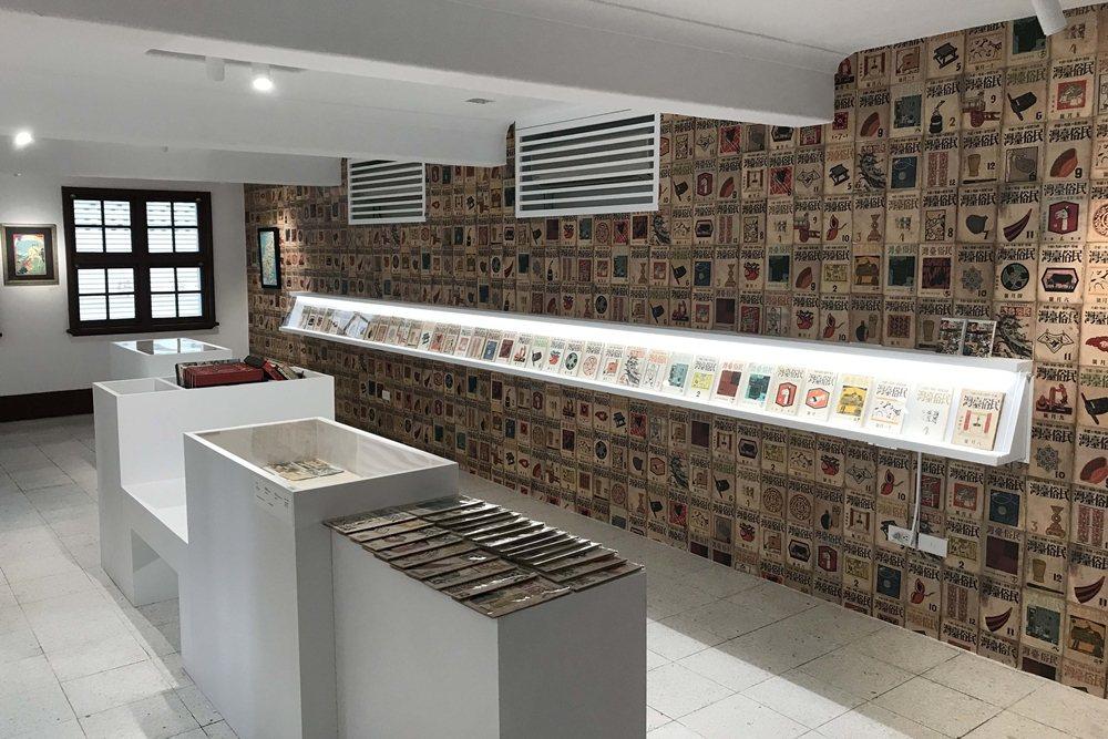 新竹州圖在書庫空間展出舊香居提供早年台灣絕版文獻,一旁牆面上則是鋪滿了「灣生」畫家立石鐵臣繪製《民俗臺灣》雜誌木刻封面。 圖/作者自攝