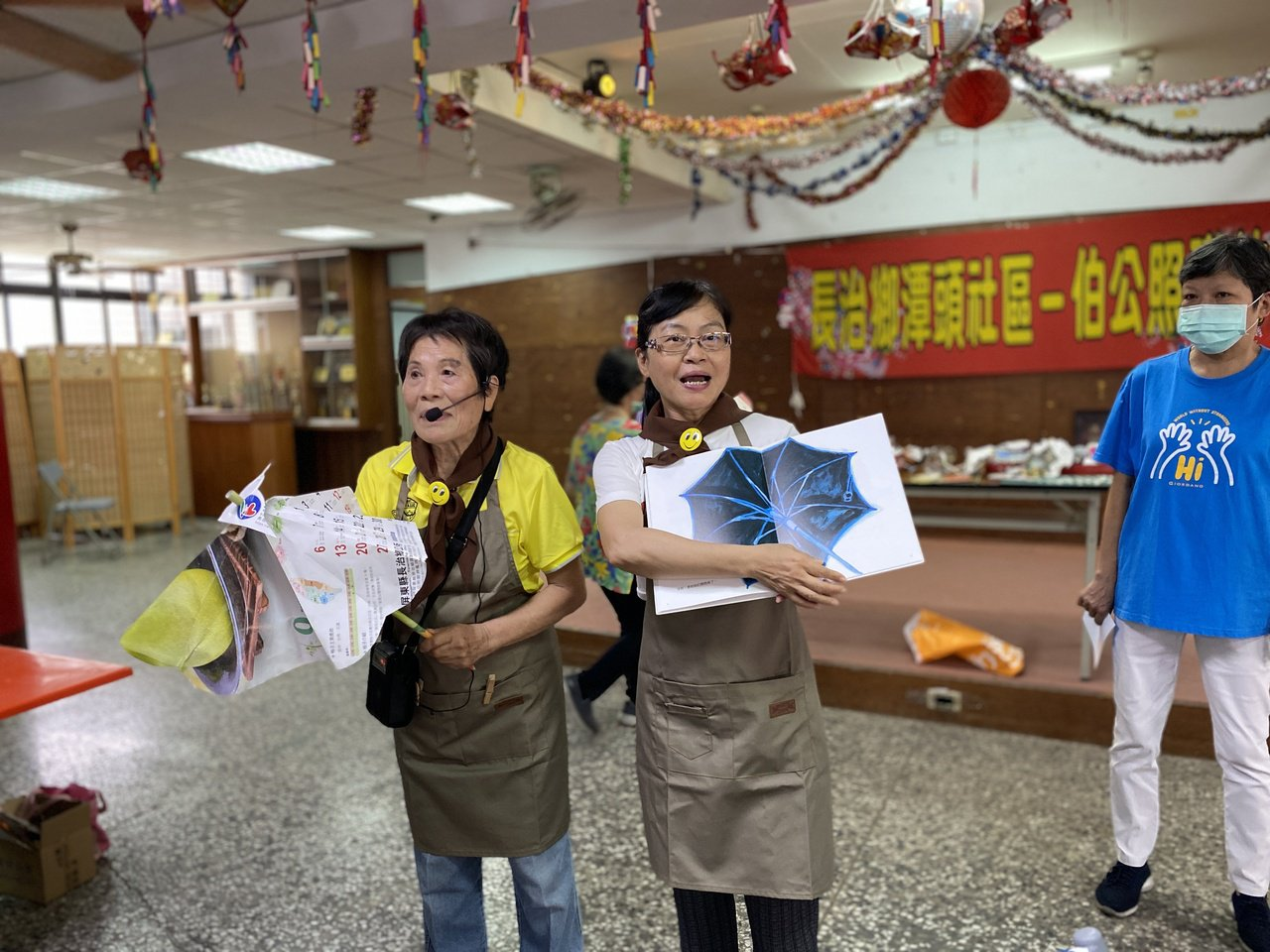 畢嘉士基金會繪本行動員曾敏(左)、高惠珠(左二)帶領長輩們製作「小紙傘」。 圖/...