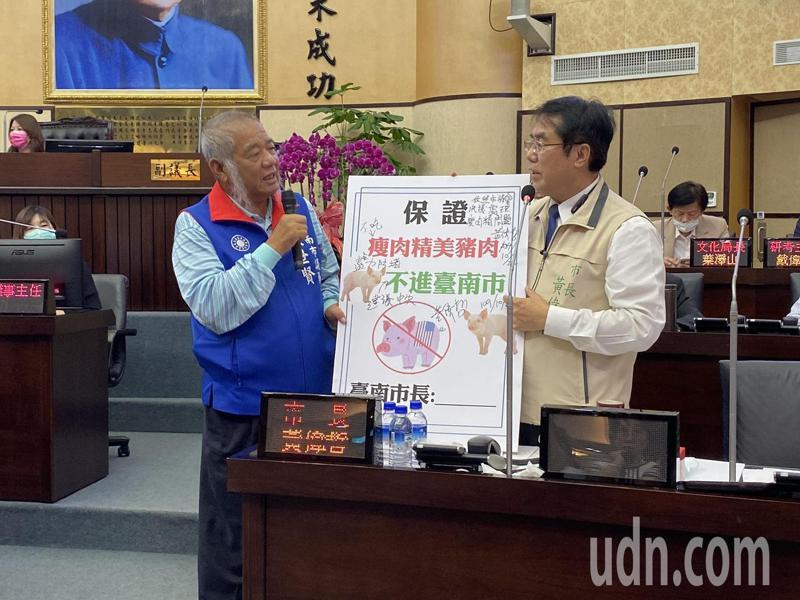國民黨台南市議員張世賢(左)要求台南市長黃偉哲(右)簽下「保證瘦肉精美豬肉不進台南市」聲明,黃偉哲用簽字筆寫下「但書」。記者鄭維真/攝影