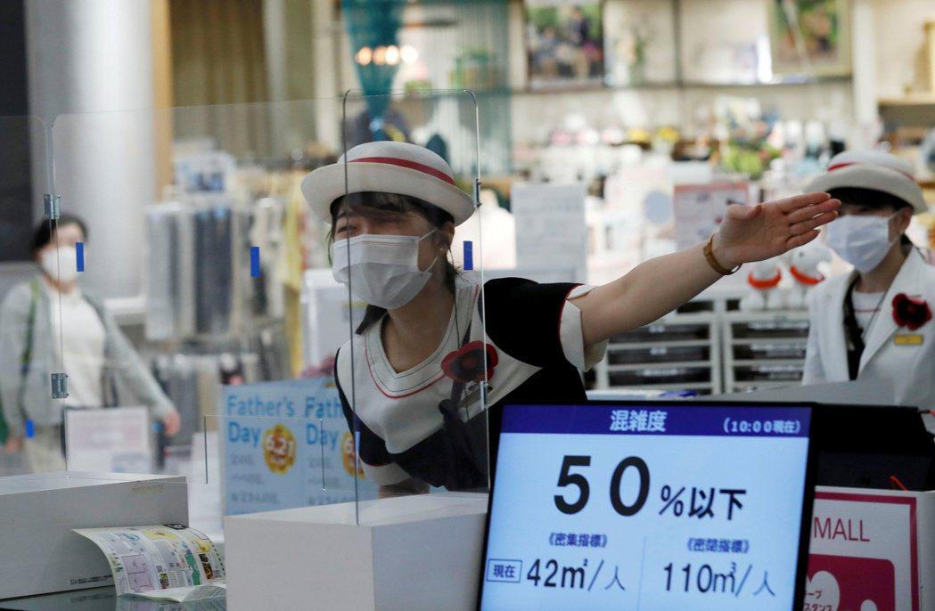 日本一家超市賣場工作人員在戴口罩與加裝隔板的多重防護下,服務顧客。(圖/路透)