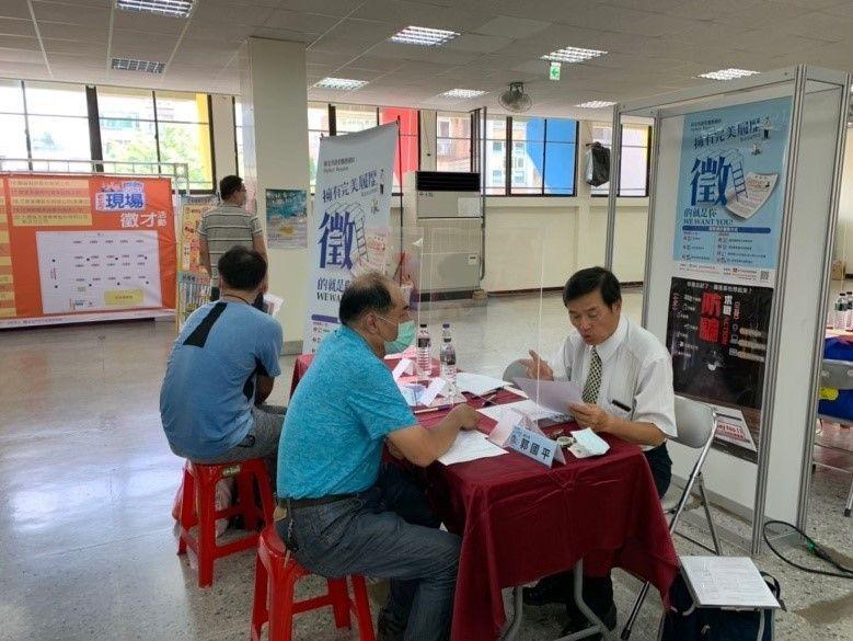 履歷健診現場服務攤位,(圖右)郭國平老師對於這次主辦單位特以隔板做防護,感到相當...