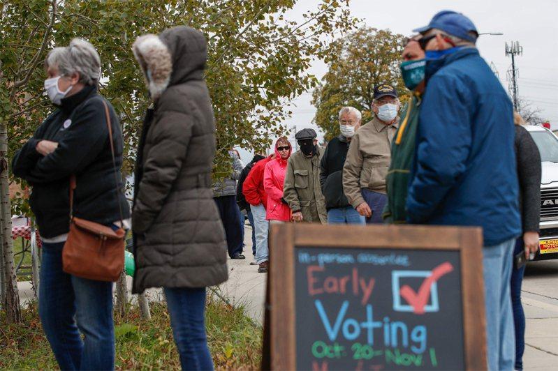 圖為搖擺州之一的威斯康辛州廿日開始舉行提前投票,密爾瓦基市選民在一處投票所外排隊。路透