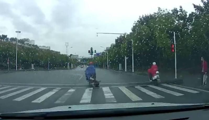 網上影片顯示,當他騎機車時,後座女童疑沒有扶穩,不小心向後摔倒在地,女童在雨中追趕機車,父親卻行駛約100米才停車,更上前一腳將女童踢倒,大聲辱罵。 圖截自/頭條日報