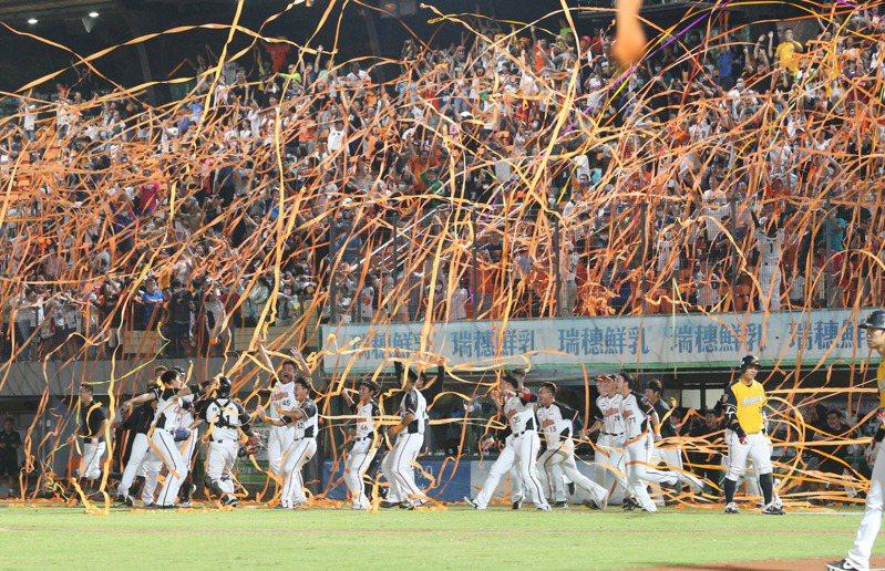 中華職棒統一獅贏得下半球季冠軍,拋下橘色彩帶。 記者劉學聖/攝影