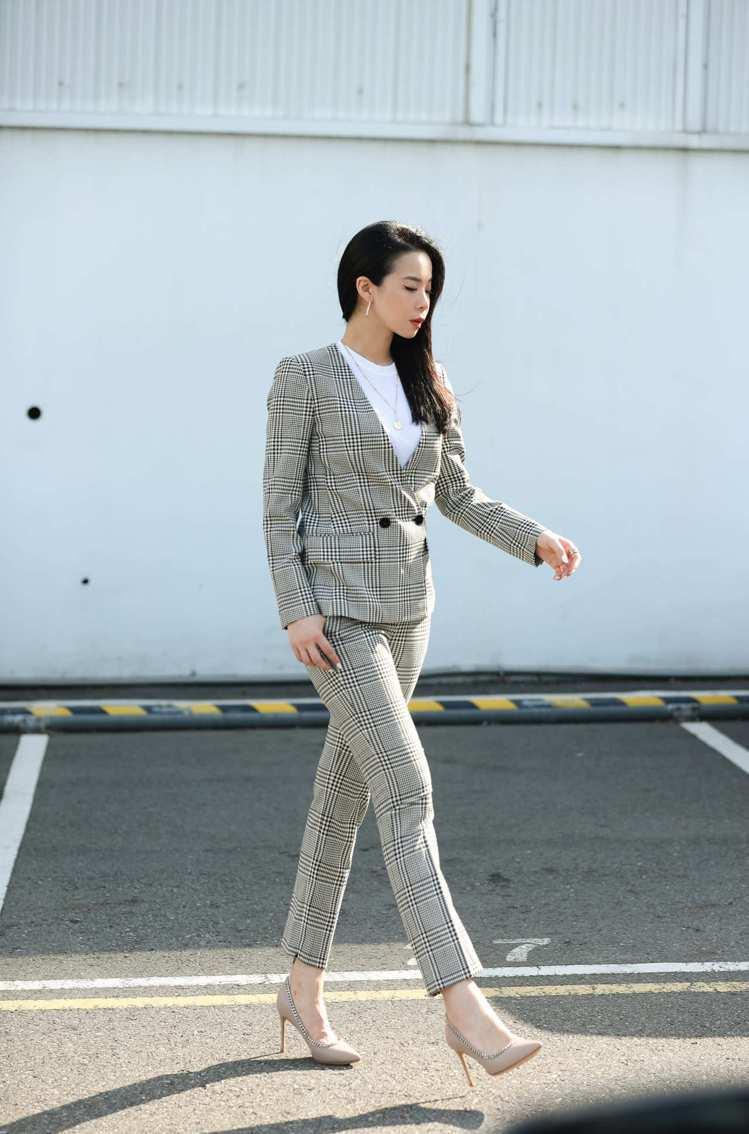 Tatler Taiwan雜誌總編輯李瑜,身穿細格紋女版西裝外套和同款長褲,內裡...