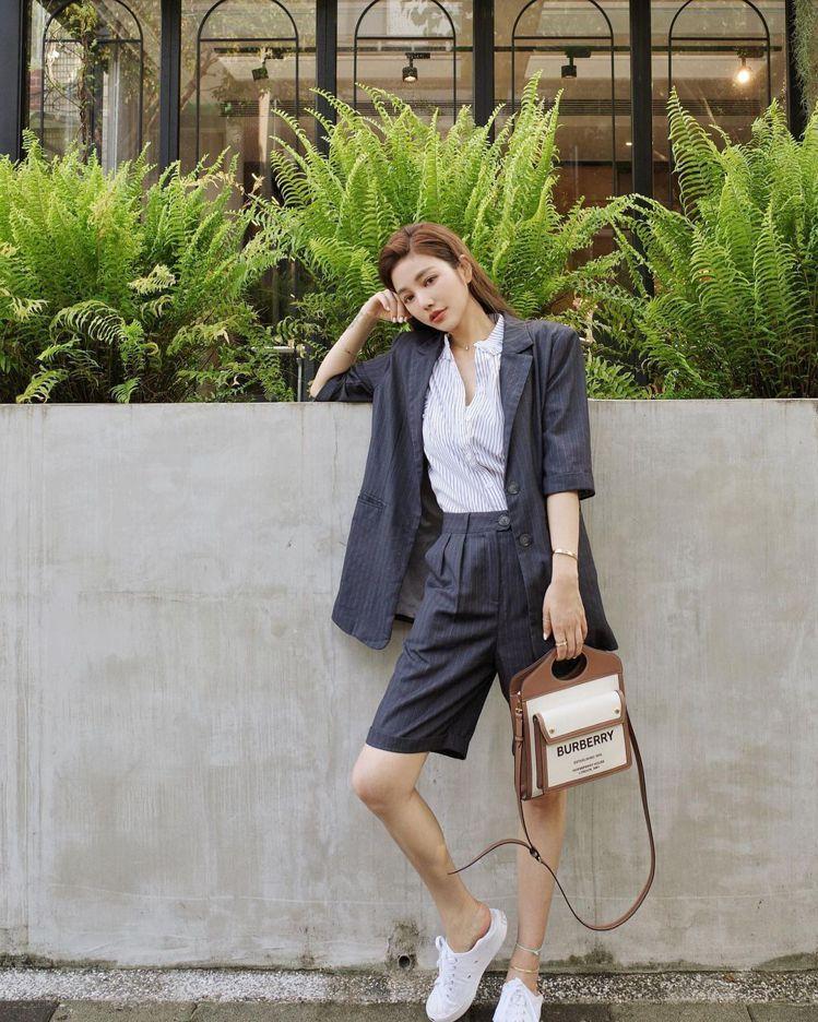 許路兒用自己品牌的深藍色條紋西裝外套配高腰短褲、帆布鞋,優雅俏皮的氣質超吸睛。圖...