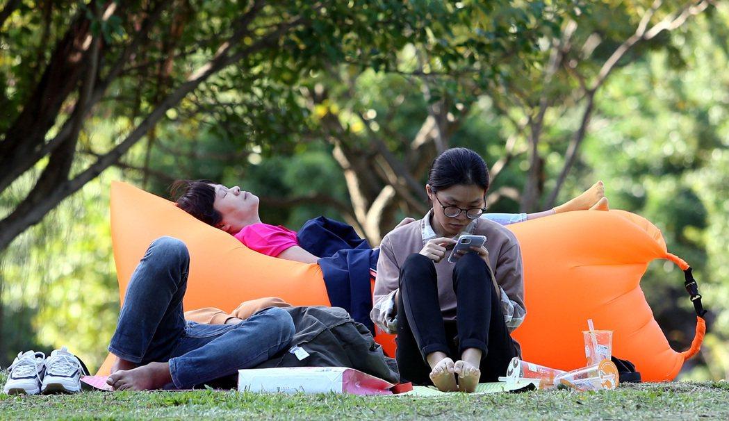今天起東北風減弱,氣溫逐漸回升,晴朗好天氣吸引民眾到綠意盎然的公園踏青休憩,躺臥...