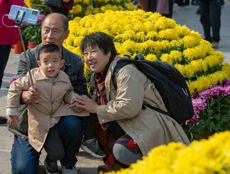 重陽節當天,市民在北京天壇公園菊花展上合影。(中新社)
