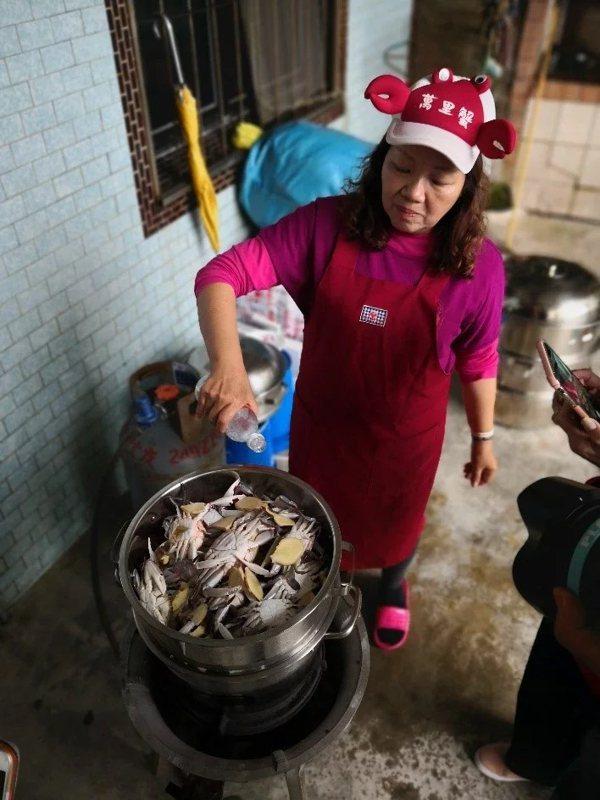 蒸煮萬里蟹之前,雪梅姐毫不猶豫將米酒和薑片揮灑到萬里蟹鍋內外。 圖/新北農業局提...